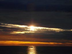 A fishing boat captured in a beam of light at sunrise. Photo