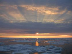 Sunset over the Arctic ice with shadow bands above and reflections on the water below. Photo