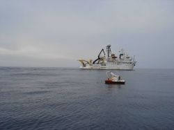 A DART II tsunami-warning buoy with the NOAA Ship OSCAR ELTON SETTE in the background. Image