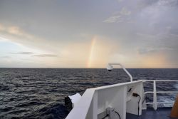 Rainbow at sunset with a small cargo ship in the distance. Photo