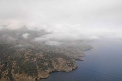Aerial view of low clouds over the rugged shoreline of Santa Cruz Island. Image