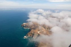Aerial view of Santa Cruz Island seen through puffy cumulus. Image