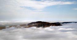 Aerial view of the high peak of Santa Cruz Island seen through a break in the clouds. Image