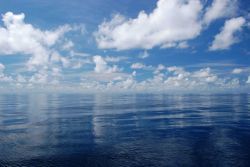Low lying fair weather cumulus and upper level altocumulus reflecting off a glassy smooth Gulf of Mexico Photo