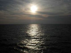 A gray colorless sunset with sunglint on the ocean surface Photo
