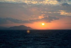 Sun setting over Tahiti on departure from Papeete. Photo