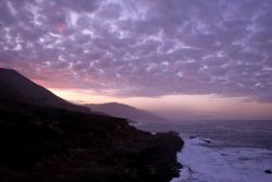 Sunrise illuminating a mackerel sky over the Big Sur coastline Photo