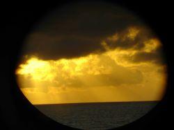 A golden sunset seen through a MILLER FREEMAN porthole. Photo