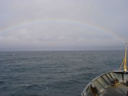 A full rainbow seen on a gray North Pacific day. Image