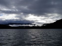 Clouds over head and fog filled valleys give a lead gray cast to Alaskan waters. Photo