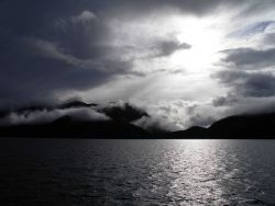A dramatic view of clouds, fog, coastal mountains, and a cloud obscured sun shining off a grey ocean. Image