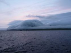 A gentle fog following topography at Dutch Harbor as a freighter leaves for an unknown port. Image