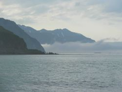 A ribbon of fog obscures the water level view in Glacier Bay. Image