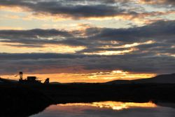 Sunset and clouds reflecting off water accented by the silhouette of an ancient gold dredge. Photo
