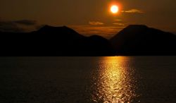 A bronze sun setting over the mountains and reflecting off the sea. Image