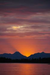 A golden Alaskan sunset seen from a quiet cove. Image