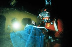 Diver prepares herring collection nets next to submersible. Photo