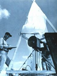 Charles Kearse, Chief Electronics Technician on the EXPLORER records tellurometer distance measurements observed by Commander Ray Stone at Swan Island Photo