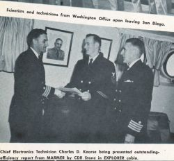 Captain Ray Stone giving Chief Electronics Technician Charles Kearse an award as Captain Emerson Jones looks on Photo