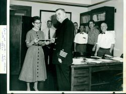 CAPT Carl Mast presenting award to member of office staff in Kansas City Regional Office. Photo