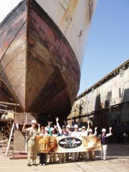 Refitting team of the NOAA Ship Okeanos Explorer beneath the bow of the ship in shipyard Photo