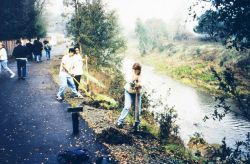 A group of student volunteers plant native trees along Brush Creek to revegetate areas along the creek that were devegetated when the waterway was cha Photo
