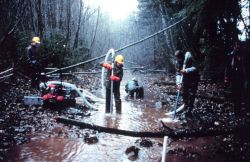 Three men in the river operate the pump. Photo