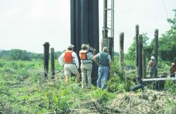 NMFS and DNR project managers inspecting installation of sheet metal which will house the SRT. Photo