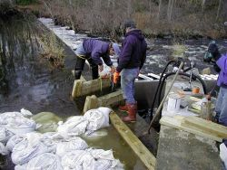 John Catena, of NOAA, supervises the crew as the ladder is being installed and fitted into the cut in the dam. Photo