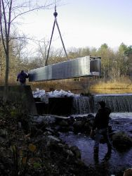 The crane lowers the first section into place, it is just about to be dropped into the notched dam. Photo
