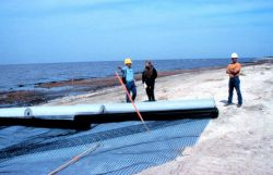Brian Kendrick, Chris Gray and a Bertucci representative standing by roles of filter cloth and geogrid on the beach. Photo