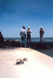 The crew discussing the filling of geotubes. Photo