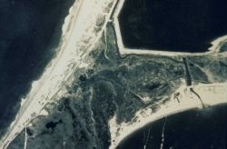 An aerial shows the marsh before it was altered by construction of a road passing through the marsh. Image