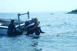 NOAA scientists prepare to receive trays of eelgrass turf for transplanting at one of the sites. Photo