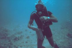 A diver equipped with underwater tape recorder, wetsuit, watch for determining dive time. Image