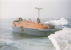 A hydrographic survey launch in Beaufort Sea ice on a raw foggy day. Image