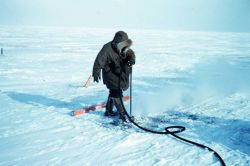 Using a boiler to melt the permafrost for setting a triangulation marker Photo