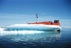 Orange, white, and blue - survey launch next to ice berg Photo