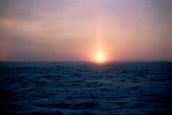 A sun pillar forms as the sun rises over the Arctic plain Photo