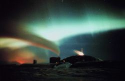 Aurora Australis - surrealistic view of South Pole station with auroral curtain and exhaust emanating in curved line fro Photo