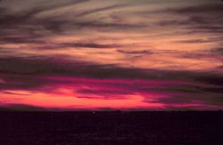 Lurid colors mark a sunrise at sea off the eastern seaboard. Photo