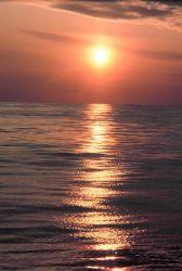 A streak of orange sunlight reflecting off the ocean at sunrise. Photo