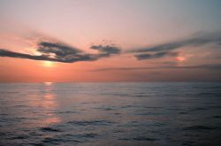 A setting sun over the ocean with a sundog to the right. Photo