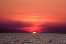 The upper limb of the sun in sight for a few more minutes over the ocean as the Earth spins rapidly away to the east. Photo