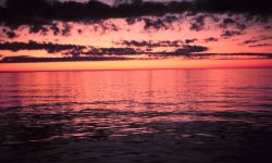 Red sky above reflecting off a red sea below. Photo