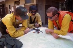 Yellowstone rangers Doug Ridley & Les Inafuku planning strategy over map at Grant Village Photo