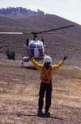 Helitack signalman signing for helicopter take off at Lamar Helibase Photo