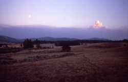 Distant smoke plume at sunset with 3/4 moon in foreground, Upper Blacktail barn Photo