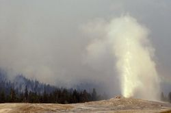 Old Faithful erupting with smoldering fire & smoke in the background Photo