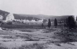 Building in meadow across from Geyser Hill, Upper Geyser Basin, inactive geyser cone in foreground (right) Photo